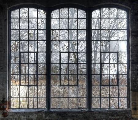 edificio industrial: Gran ventana con los cristales rotos Antiguo en una sala desierta Foto de archivo