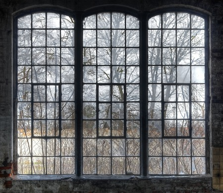Old large window with broken panes in a deserted hall Stockfoto