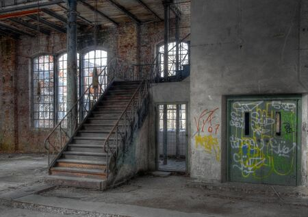 Old stairway next to an elevator in a deserted hall