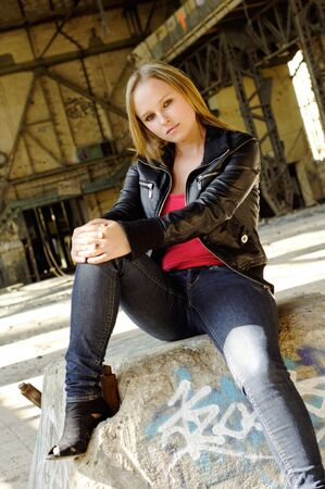 Young woman with a leather jacket in a deserted hall photo