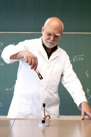 男加熱するブンゼン バーナーとワイヤ 写真素材