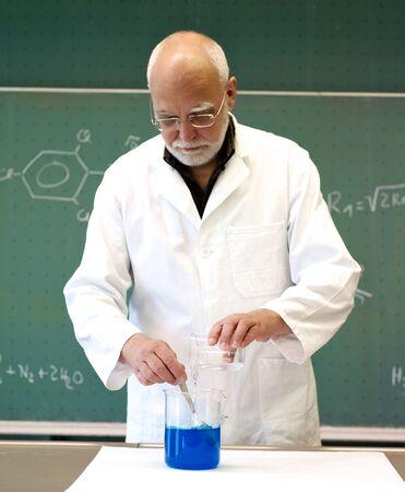 ガラスのフラスコの中の化学物質を混合先生