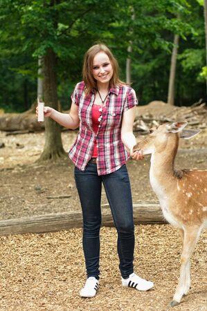 女性は笑って、若い鹿の餌