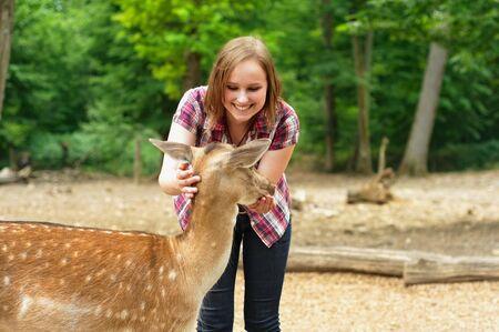 女性摂食と若い鹿をなでる
