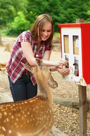 自販機からペットフードを取る女性