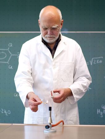 研究室で男にブンゼン バーナーが点灯しています。