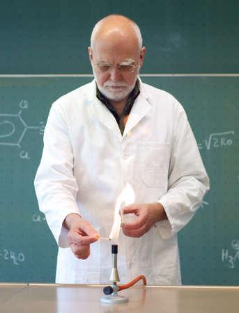 ブンゼン バーナーに火を付ける男性の科学者