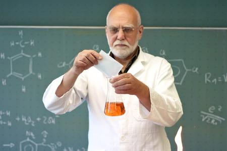 先生がガラスのフラスコの中の異なった化学薬品をミックスします。 写真素材
