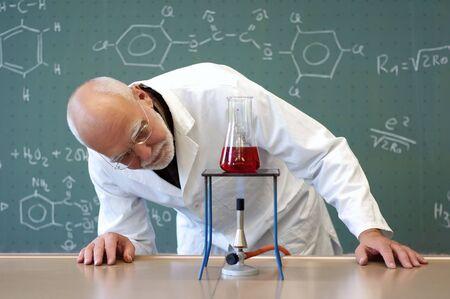 男はガラスのフラスコの化学物質の加熱 写真素材