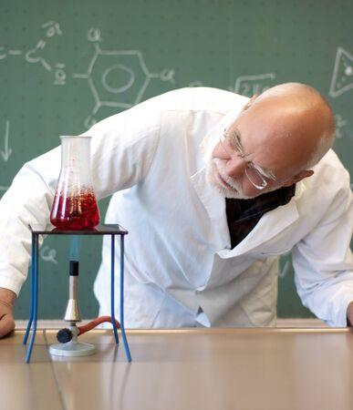 男を調べガラス フラスコの加熱された化学物質