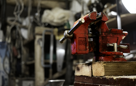 greased: Red vice. Greased and dirty. In background out of focus workshop interior