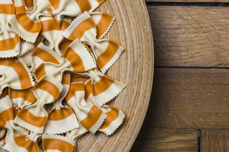 plater: Pasta bows on a wooden plater on top of wooden background Stock Photo