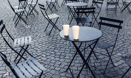 Chairs and tables scattered on pavement on early morning Stock Photo