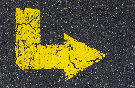 Yellow arrow painted on tarmac