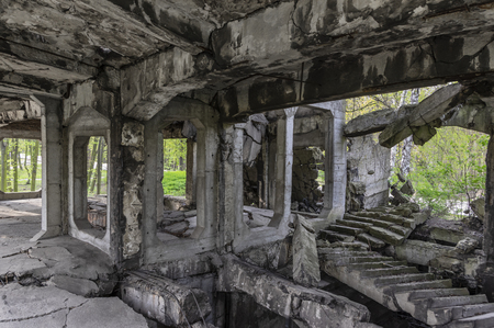 Interior of ruined, concrete building, abandoned in forest Фото со стока