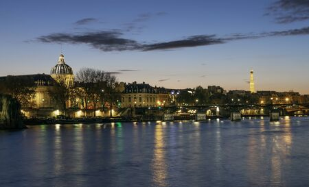 Paris, France - November 05, 2019: Bank of Seine River in Paris in the evening. Among buildings there is dome of French Institute and in distance Eiffel Tower 版權商用圖片 - 136135869