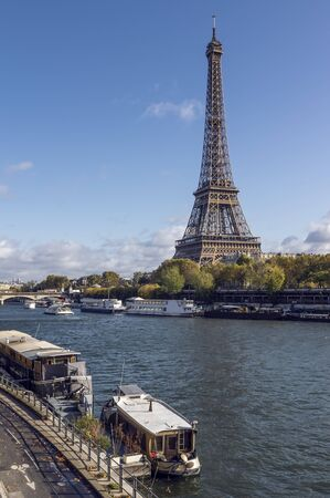 Eiffel tower across Seine River, in foreground are parked boats