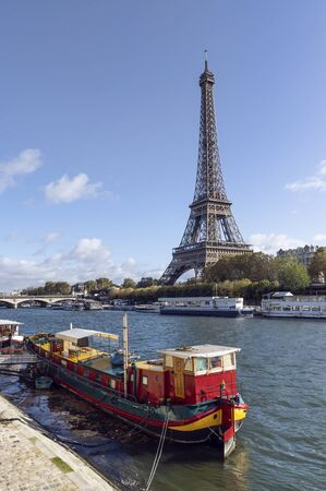 Eiffel tower across Seine River, in foreground are parked boats 版權商用圖片 - 134334940