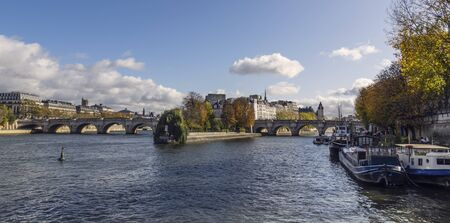 Pont Neuf bridge and island on Seine River in Paris city center. Taken from a boat on sunny autumn day