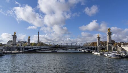 Pont Alexandre III seen from the boat. In distance there is of Eiffel tower showing up. The most extravagant bridge of Paris 版權商用圖片