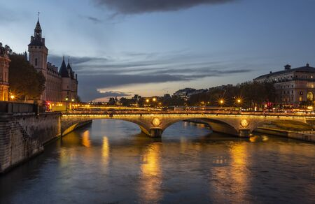 Stone bridge Pont au Change in Paris at the dusk. On the left are towers of Conciergerie, on right northern bank of river Seine