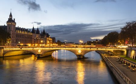 Stone bridge Pont au Change in Paris at the dusk. On the left are towers of Conciergerie, on right northern bank of river Seine 版權商用圖片 - 134334953