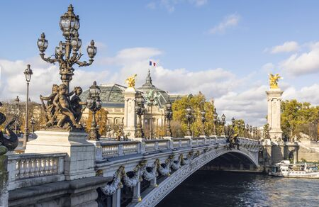 Famous Pont Alexandre III bridge on sunny autumn day. Behind is roof of Grand Palais with French flag waiving against clouds 版權商用圖片 - 134334954
