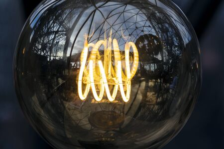 Close up on fancy, spiral, filament of a glowing light bulb 版權商用圖片 - 134333239