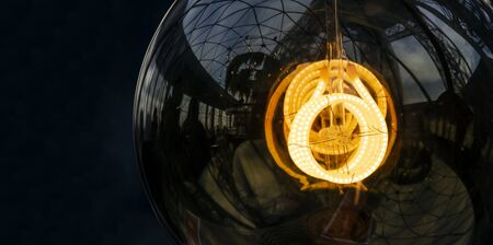 Close up on fancy, spiral, filament of a glowing light bulb 版權商用圖片 - 134332221