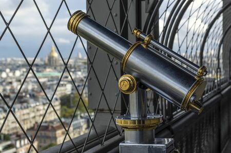 Retro styled tourist telescope on Eiffel Tower. Behind bars is out of focus view of Paris on sunny autumn day 版權商用圖片 - 134332218