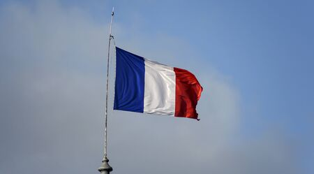 Flag of France waiving against sky on windy day