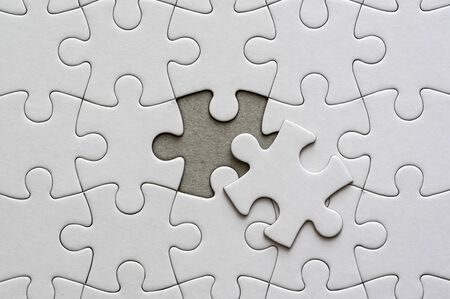 Close up on blank, white jigsaw puzzle pieces. One piece is removed, to the side 版權商用圖片 - 140669793