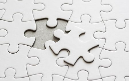 Close up on blank, white jigsaw puzzle pieces. One piece is removed, to the side 版權商用圖片 - 140669832