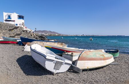 Small boats on a shore in harbor of Playa Blanca. City and the shore are seen in distance 版權商用圖片 - 140037663