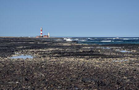 Rocky coast leading to El Toston Lighthouse in Fuerteventura Island Stock fotó