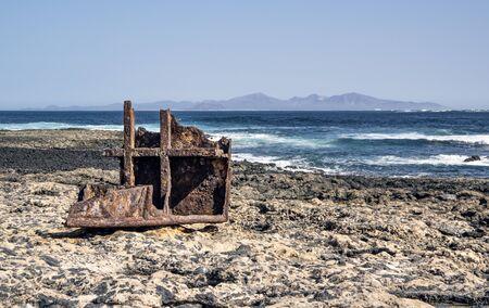 Piece of rusty boat on a shore of Fuerteventura Island. On the horizon is Lanzarote Island 版權商用圖片 - 140195527
