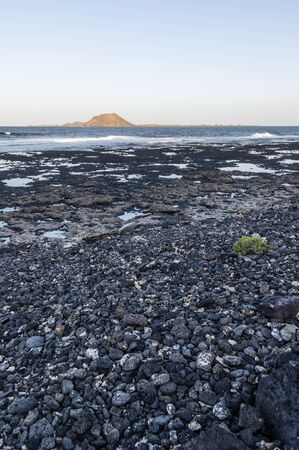 Black shore in Corralejo, on horizon is Isla de Lobos in evening sun