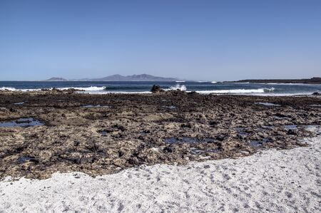 Shore of Fuerteventura with Lanzarote Island visible in the distance 版權商用圖片 - 140195487