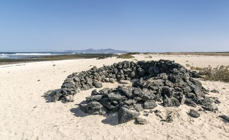 Ring of stones built as a cover from wind on sandy beach in Fuerteventura Island 版權商用圖片 - 140195672
