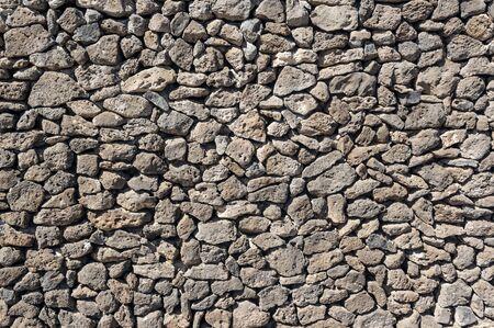 Texture of stone wall made of volcanic rocks 版權商用圖片 - 140351248