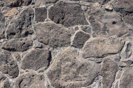Texture of stone wall made of volcanic rocks 版權商用圖片 - 140351220