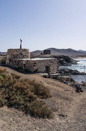 Not working lime kiln in front. Behind is old coastal fort called Castillo de El Toston in El Cotillo, Fuerteventura Island