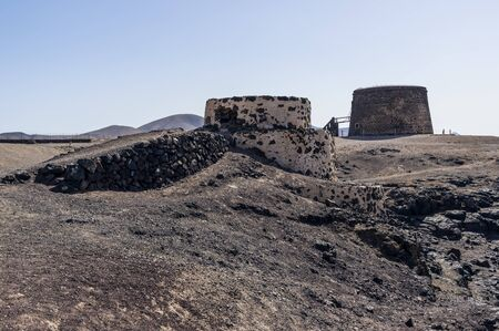 Not working lime kiln in front. Behind is old coastal fort called Castillo de El Toston in El Cotillo, Fuerteventura Island 版權商用圖片 - 140562150