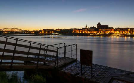 Toruń seen at the dusk across Vistula River. In front is small mooring platform