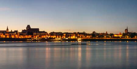 City of Toruń at dusk seen across Vistula River