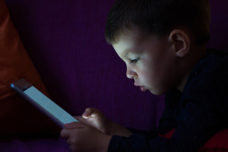 lying in bed: Cute kid with tablet in the dark