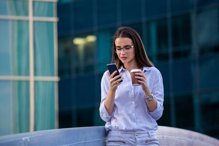Executive business woman looking at mobile smartphone and drinking coffee from disposable paper cup in the street with office buildings in the background.