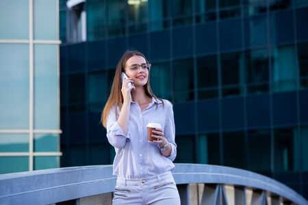 Executive business woman talking on mobile smartphone and drinking coffee from disposable paper cup in the street with office buildings in the background. Imagens
