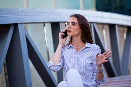 Business woman recieving bad news on smartphone in the street with office buildings in the background.