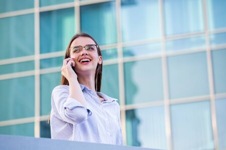Happy smiling business woman talking on mobile smartphone in the street with office buildings in the background.